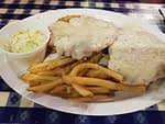 chicken fried steak with gravy and fries and coleslaw
