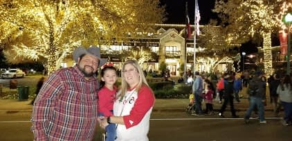 family posing for picture with Dickens on Main in Boerne lights on